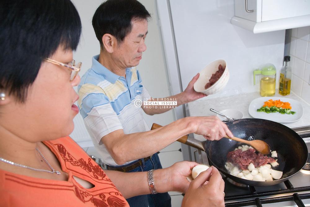 Couple preparing meal of beef in black bean sauce,