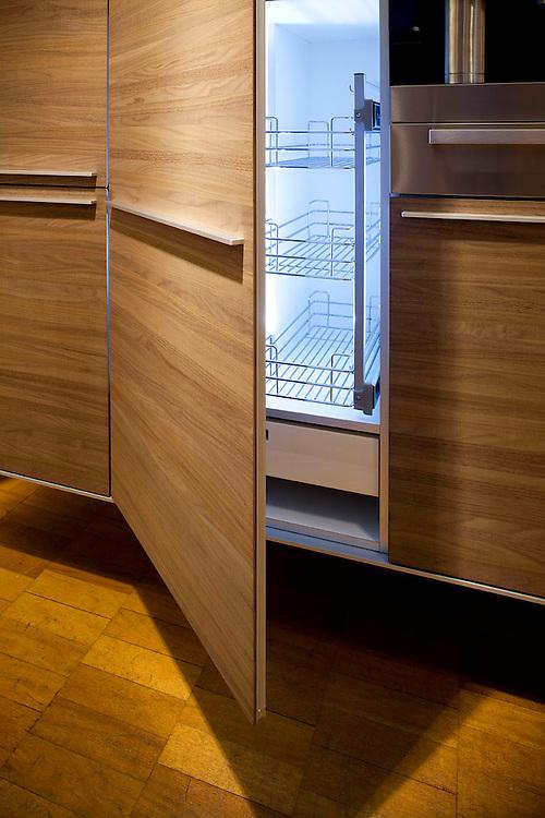 Lit up fridge interior with wooden door and wooden kitchen units