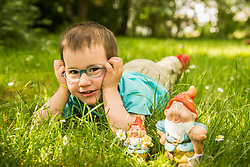 Smiling little boy lying in the meadow with garden gnomes