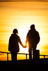 © Licensed to London News Pictures. 02/10/2016. Southsea, Hampshire, UK.  A couple hold hands during an evening walk on what has been another warm and sunny autumn day in the South of England. Photo credit: Rob Arnold/LNP
