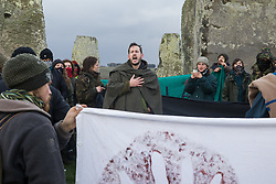 Salisbury, UK. 5th December, 2020. A man addresses over one hundred people, including local residents, climate and land justice activists and pagans, during a Mass Trespass at Stonehenge. The trespass was organised in protest against the approval by Transport Secretary Grant Shapps of a £1.7bn project for a two-mile tunnel beneath the World Heritage Site and a further eight miles of dual carriageway for the A303, as well as the government's £27bn Road Investment Strategy 2 (RIS2).