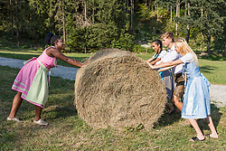Teenage friends pushing straw bale, Bavaria, Germany