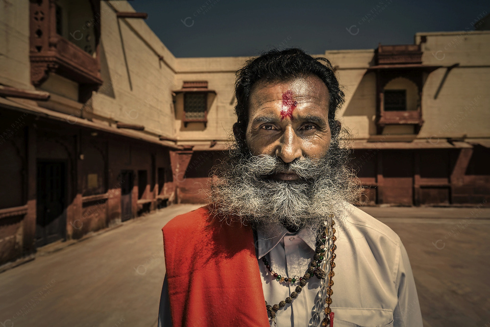 """Priest in courtyard of Fort Pokaran India. This 14th century citadel also known as """"Balagarh"""" in the Thar Desert is the premier fort of The Chief of  Mighty Champawats. With its beautiful red color it once stood in the silk and other goods route to Persia and beyond"""