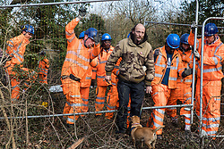 Harefield, UK. 7 February, 2020. An activist holds Heras fencing being erected by HS2 engineers to surround three environmental activists from Extinction Rebellion who have climbed a veteran oak tree close to the Harvil Road wildlife protection camp in order to try to protect it from felling. HS2 are expected to try to fell large numbers of mature trees in the immediate vicinity over the weekend even though the high-speed rail link is still awaiting Boris Johnson's approval.