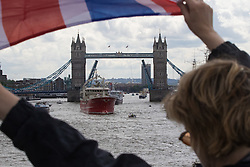 London Bridge, London, June 15th 2016. A flotilla of fishing boats led by UKIP's Nigel Farage heads through Tower Bridge in protest against the EU's Common Fisheries Policy and in support of Britain leaving the EU. PICTURED: A supporter of the Leave campaign waves her flag as the fleet enters the Pool of London.