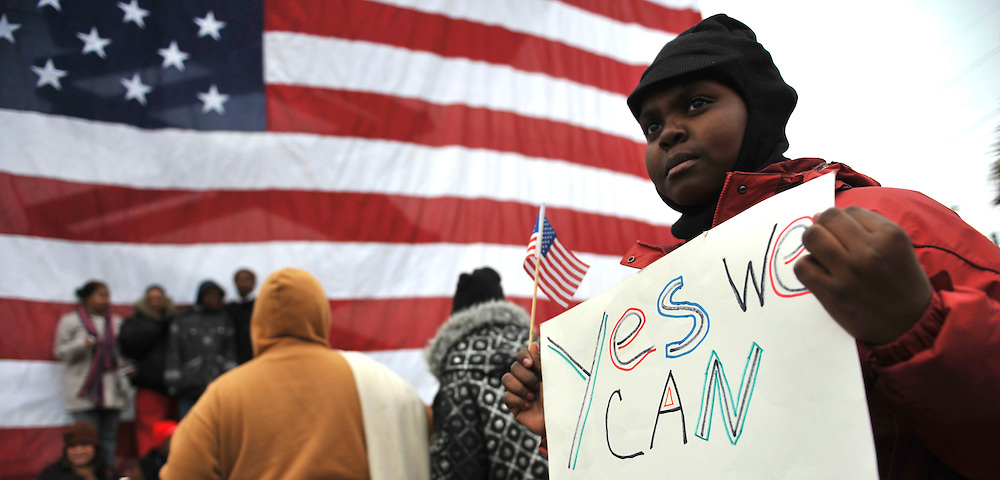 """Zoi Council, 10, from nearby Newcastle, holds a """"Yes We Can,"""" Obama campaign slogan, poster, posing for pictures in front of a large American flag at the conclusion of President-elect Obama's pre-inauguration rally in Wilmington, Delaware,  where a crowd of thousands braved sub-zero temperatures to lend their support.  Obama, Vice President-elect Biden and their families traveled by train on a Whistle Stop Tour, opening Inauguration celebrations with rallies in Philadelphia, Wilmington, and Baltimore before their final arrival in Washington, D.C.  The inauguration takes place on January 20, 2009, swearing Obama in as the 44th President of the United States of America.¬?"""