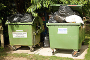 Trade waste wheelie bins overflowing with rubbish bags