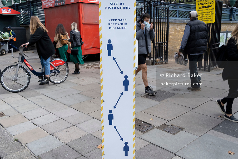 As the UK once again experiences regional rises in infection rates (R numbers), a man puts on his face covering while walking past a sign urging Londoners to keep their social distance while walking on Piccadilly, on 1st October 2020, in London, England.