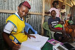 Violet Nyamwanya talks with women and lenters details in record Books at the MMS ANC outreach Clinic. SAHFA baseline survey visit to Angiya, Homa Bay County, Kenya.  SAHFA Kenya © April 2019