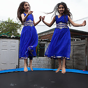 Southall, Greater London, UK, August 11, 2015.<br /> At home with the Sidhu family in Southall. Navneet (11) and Prbdeep (10) have a lot of energy. They are both excellent students, Navneet wants to become a pilot, and Prbdeep a makeup artist.<br /> <br /> Southall, Greater London, UK, August 11, 2015.<br /> Nel giardino della famiglia Sidhu residente a Southall. Le due ragazze, Navneet (11) e Prbdeep (10) hanno molta energia, sono studentesse efficienti e Navneet desidera diventare pilota mentre Prbdeep una make up artist.