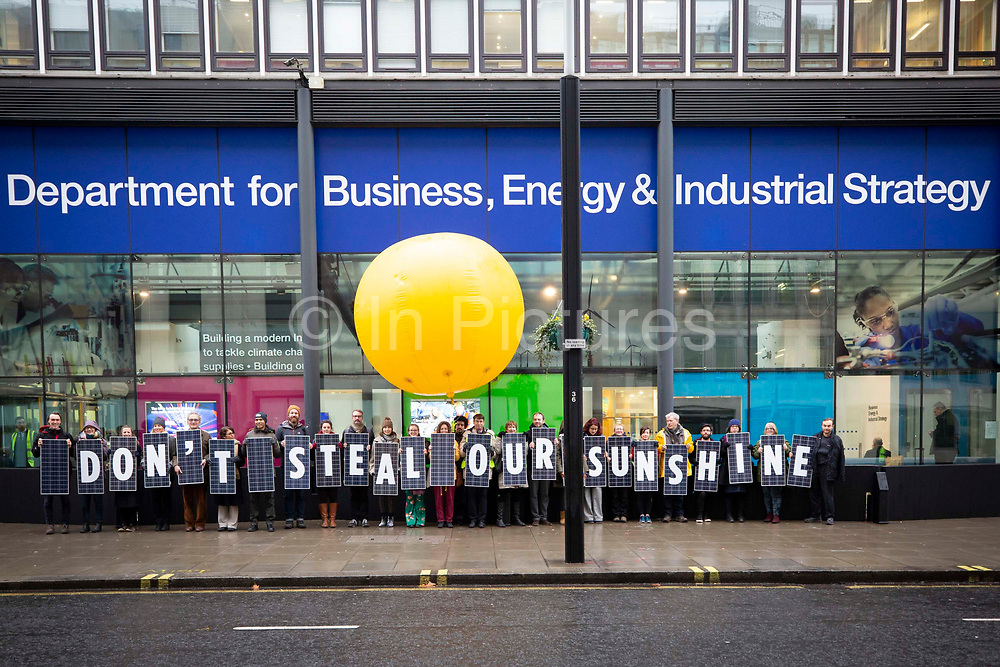 Campaigners protest outside the Department for Business, Energy & Industrial Energy BEIS with the words 'Don't Steal Our Sunshine' written on solar panels on 5th December 2018 in Westminster, London. United Kingdom. They are calling on the government to stop their plans to axe the export tariff. The tariff pays small scale solar owners for their excess energy. Climate campaign group 10:10 also covered Old Palace Yard outside the House of Commons with dozens of solar panels held by climate activists, Westminster, London. United Kingdom.