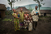 Mapendo Sakina, 20, far left, stands in her family's courtyard with her mother, other siblings, and her father, far right, who is a pastor in Kichanga. The father once disowned her after learning she was pregnant from the rapes, but accepted her after she gave a birth. He had her younger sister quit the school to pay for Mapendo's education and to help her become a math teacher.