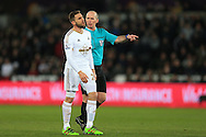Referee Mike Dean makes his point to a frustrated Angel Rangel of Swansea city. Barclays Premier league match, Swansea city v Aston Villa at the Liberty Stadium in Swansea, South Wales on Saturday 19th March 2016.<br /> pic by  Andrew Orchard, Andrew Orchard sports photography.