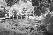 Sheepwash Bridge, a 17th Century packhorse bridge, on a summer's day in Ashford in the Water. Infrared capture of this classic White Peak scene, Peak Dsitrict National Park, Derbyshire, England, UK. August, 2014.