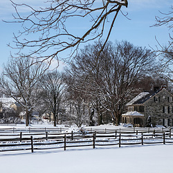 A stone house and fences after a blanket of snow.
