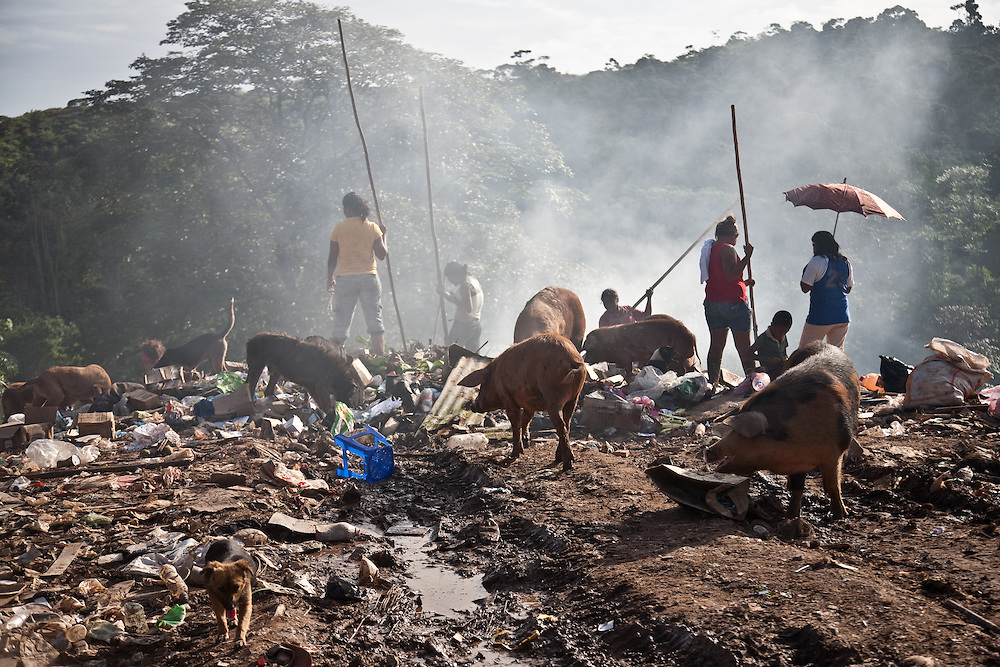 mucking in: women and children scavenge for pieces of metal, aluminium cans and other useful items they may be able to collect and then sell on in a market affected not only by local demand but also global commodity prices.