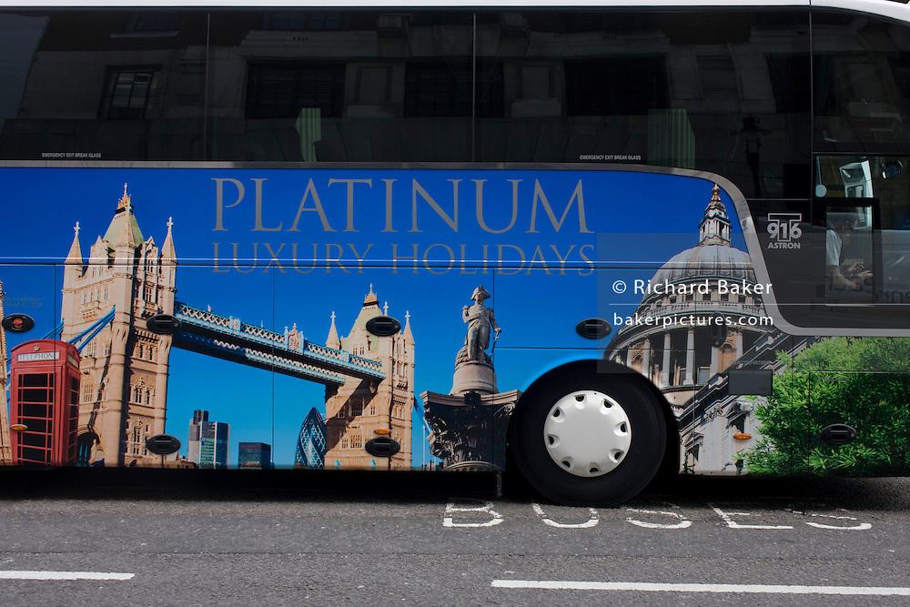 A parked tour coach for Platinum Holidays features famous London landmarks awaits passengers outside a London theatre.