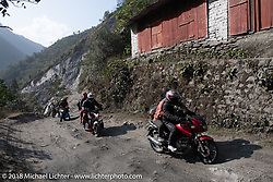 Locals ride by on Day-7 of our Himalayan Heroes adventure riding from Tatopani to Pokhara, Nepal. Monday, November 12, 2018. Photography ©2018 Michael Lichter.