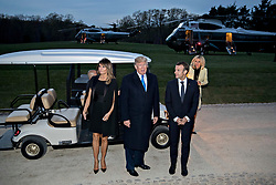 U.S. President Donald Trump speaks to members of the media next to a golf cart following a dinner with Emmanuel Macron, France's president, right, and U.S. First Lady Melania Trump, left, at the Mount Vernon estate of first U.S. President George Washington in Mount Vernon, Virginia, U.S., on Monday, April 23, 2018. As Macron arrives for the first state visit of Trump's presidency, the U.S. leader is threatening to upend the global trading system with tariffs on China, maybe Europe too. Photographer: Andrew Harrer/Bloomberg
