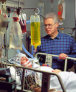 A concerned man watches over his wife in a intensive care unit. Medicine, medical, health care, caring, illness, trauma, accident, life, death, dying, hospital, love, life support, ethics, intravenous.