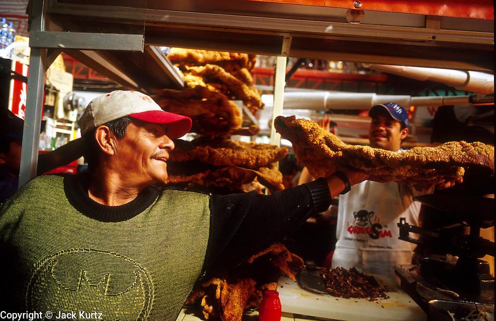 16 JANUARY 2002, GUANAJUATO, GUANAJUATO, MEXICO:  A chicharone (fried pork skins) salesman makes a delivrey to a snack bar in Mercado Hidalgo, opened in 1910, in the city of Gunajuato, state of Guanajuato, Mexico, Jan. 16, 2002. Mercado Hidalgo is the main market for Guanajuato..PHOTO BY JACK KURTZ
