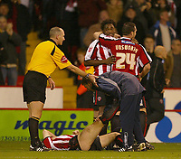 Photo: Aidan Ellis.<br /> Sheffield Utd v Luton Town. Coca Cola Championship.<br /> 01/11/2005.<br /> Sheffield's Vincent Perigard celebrates his goal an teams third with David Unsworth as Derek Greary lies injured on the floor after providing the cross for the goal