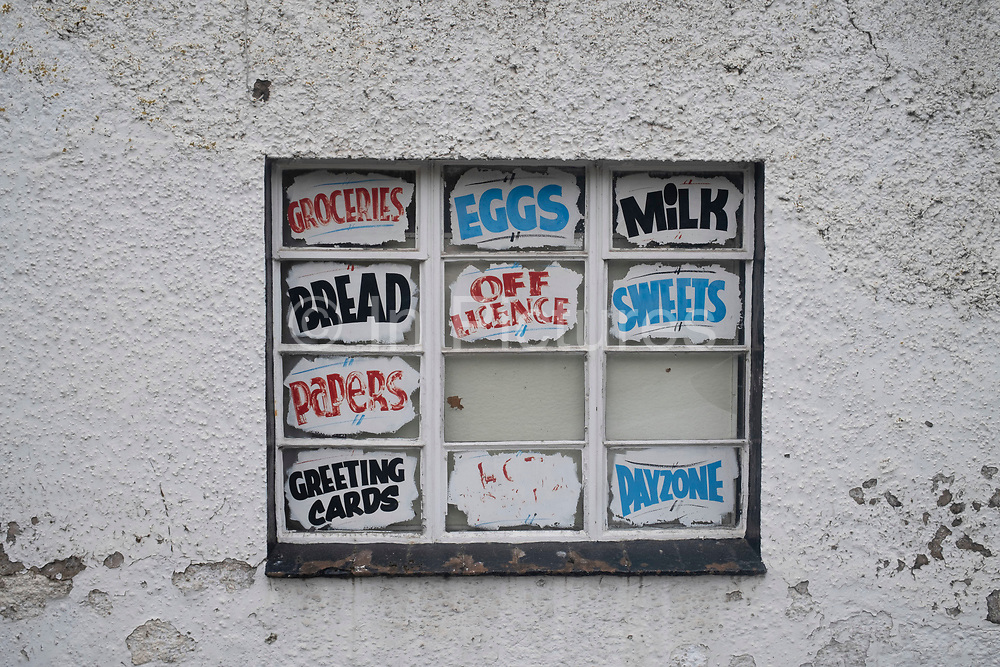 Old fashioned and faded signs in a small convenience store window on 7th June 2021 in Hereford, United Kingdom. Various staples of British life were on sale here including: bread, milk, groceries, eggs, as well as less important items like newspapers, greetings cards, sweets and off license goods.