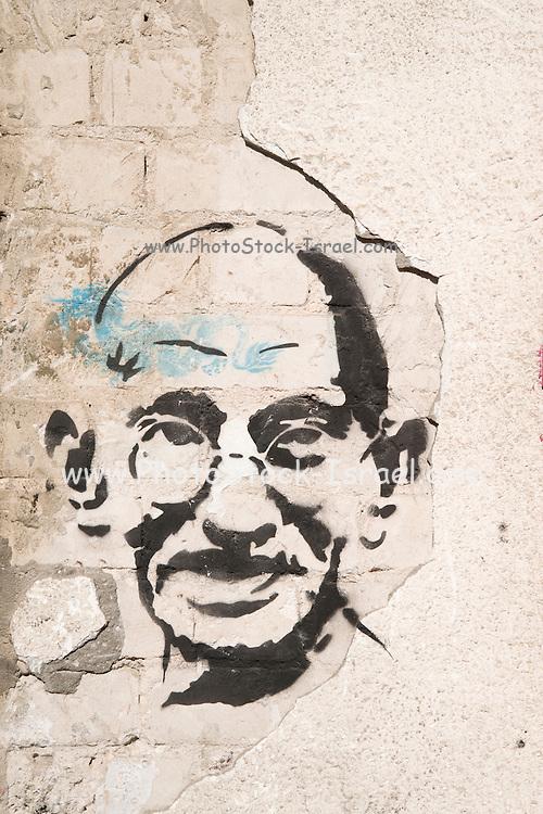 Israel, Tel Aviv, Graffiti of Mahatma Gandhi on an old dilapidated cracked wall