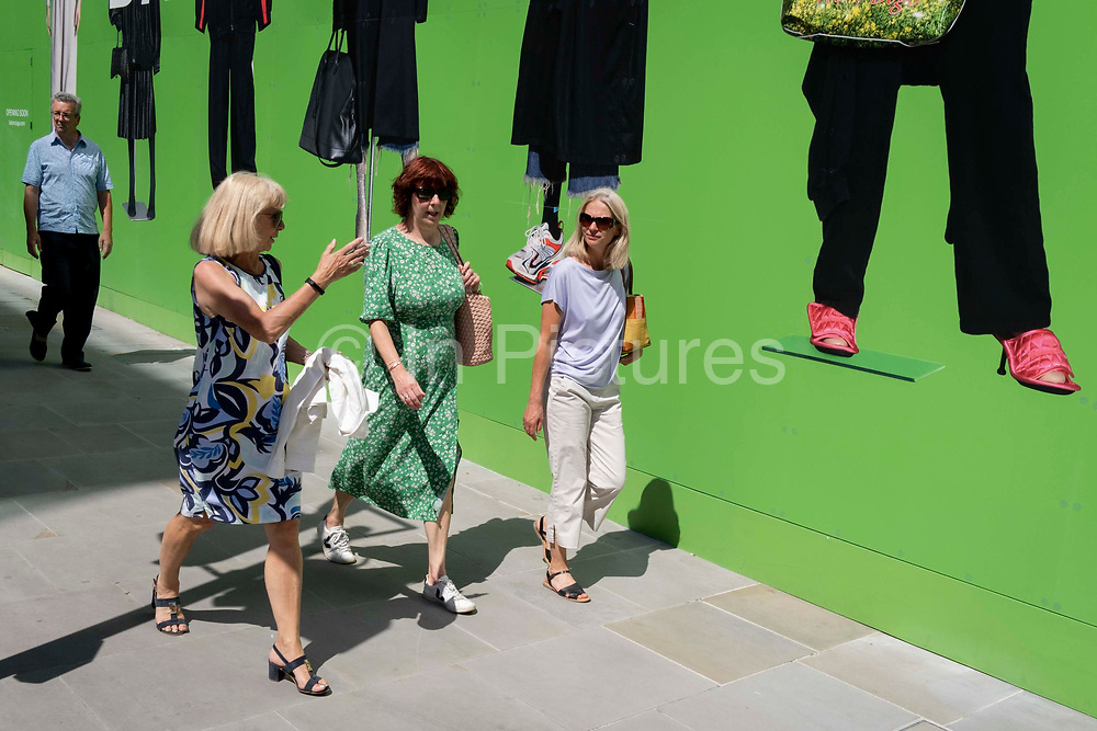 Shoppers beneath the temporary hoarding for Balenciaga, a retail space which is opening soon on Bond Street, on 16th July 2021, in London, England. Balenciaga is a fashion house founded in 1917 by Spanish designer Cristóbal Balenciaga in San Sebastián, Spain.