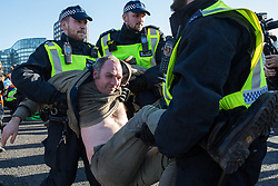 London, UK. 17th November, 2018. Police officers arrest a man after environmental campaigners from Extinction Rebellion blocked Lambeth Bridge, one of five bridges blocked in central London, as part of a Rebellion Day event to highlight 'criminal inaction in the face of climate change catastrophe and ecological collapse' by the UK Government as part of a programme of civil disobedience during which scores of campaigners have been arrested.