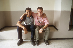 Two teenage boys sitting arm in arm smiling,