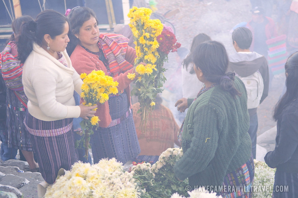 Women selling flowers in the Chichicastengo market. They are on the front steps of Santo Tomas Church and the smoke is from local Maya prayer leaders (known as chuchkajaues) burning incense and copal resin. Chichicastenango is an indigenous Maya town in the Guatemalan highlands about 90 miles northwest of Guatemala City and at an elevation of nearly 6,500 feet. It is most famous for its markets on Sundays and Thursdays.