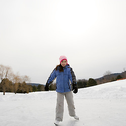 A young girl (age 9) ice skates oin a frozen pond in Quechee, Vermont.