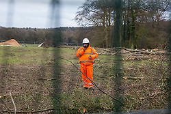 Wendover, UK. 9th April, 2021. A HS2 security guard uses a mobile phone to film a press photographer from a site alongside the A413 where mature trees have recently been felled for the HS2 high-speed rail link. Tree felling work for the project is now taking place at several locations between Great Missenden and Wendover in the Chilterns AONB, including at Jones Hill Wood.
