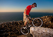 Andrew Guess (26) of Gardens rides his trial bicycle on the granite outcrop above the Atlantic Seaboard. Mountain bike trials, also known as observed trials is a discipline of mountain biking in which the rider attempts to pass through an obstacle course without setting foot to ground. Derived from motorcycle trials, it originated in Spain and is said to have been invented by the father of Ot Pi, a world champion motorcycle trials rider. Pi's father had wanted his son to learn motorcycle trials by practising on an ordinary push bike..Trials riding is an extreme test of bicycle handling skills, over all kinds of obstacles, both natural and man-made. It now has a strong -- though small -- following worldwide, though it is still primarily a European sport. Skills taken from trials riding can be used practically on any bicycle for balance, for example controlled braking and track standing, or balancing on the bike without putting a foot down. Competition trial bikes are characterised by powerful brakes, wide handlebars, lightweight parts, single-speed low gearing, low tyre pressures with a thick rear tire, distinctive frame geometry, and typically a lack of seat. Andrew is one of a hanful of trial riders in South Africa. Picture by Greg Beadle