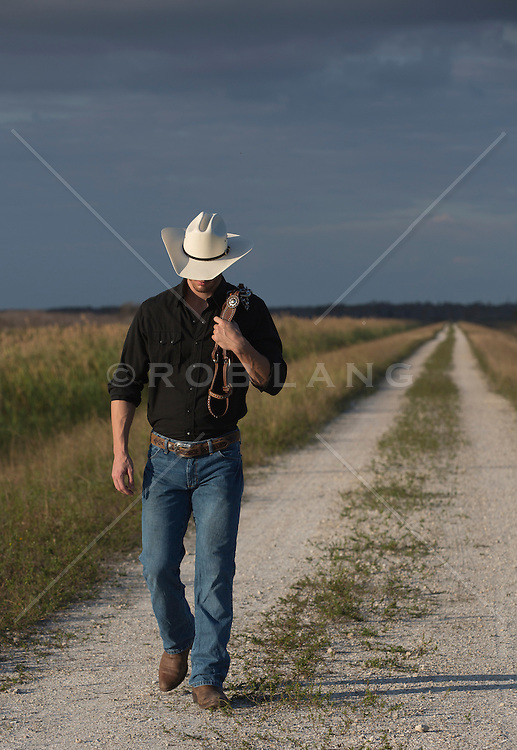 All American cowboy on a dirt road at sundown