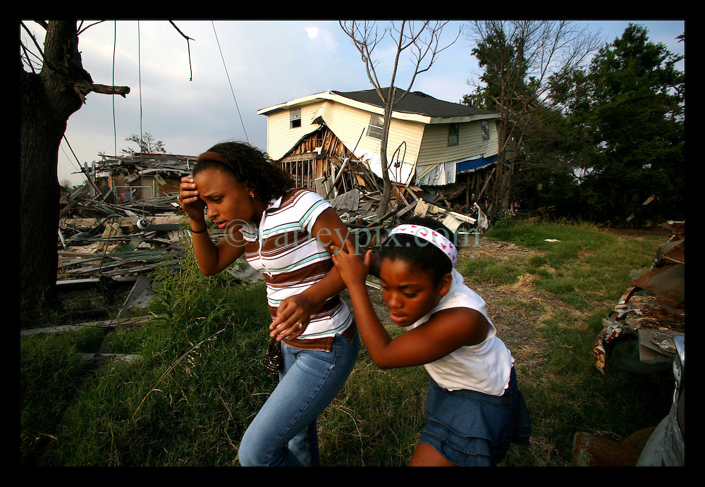 1 June, 2006. Lower 9th Ward, New Orleans, Louisiana. First day of hurricane season. L/R; Children of the storm return home. Ariana Murph (13 yrs) and her friend Renisha Menendez (11 yrs) escape a biting insect as they walk through piles of wreckage of what used to be Ariana's home at 1739 Jourdan Ave in the devastated Lower 9th Ward. Photographed is the area where a huge barge smashed through the original flood wall, where a tidal wave of water rushed through, devastating the area where so many people died. Four of Ariana's neighbours perished in the storm.