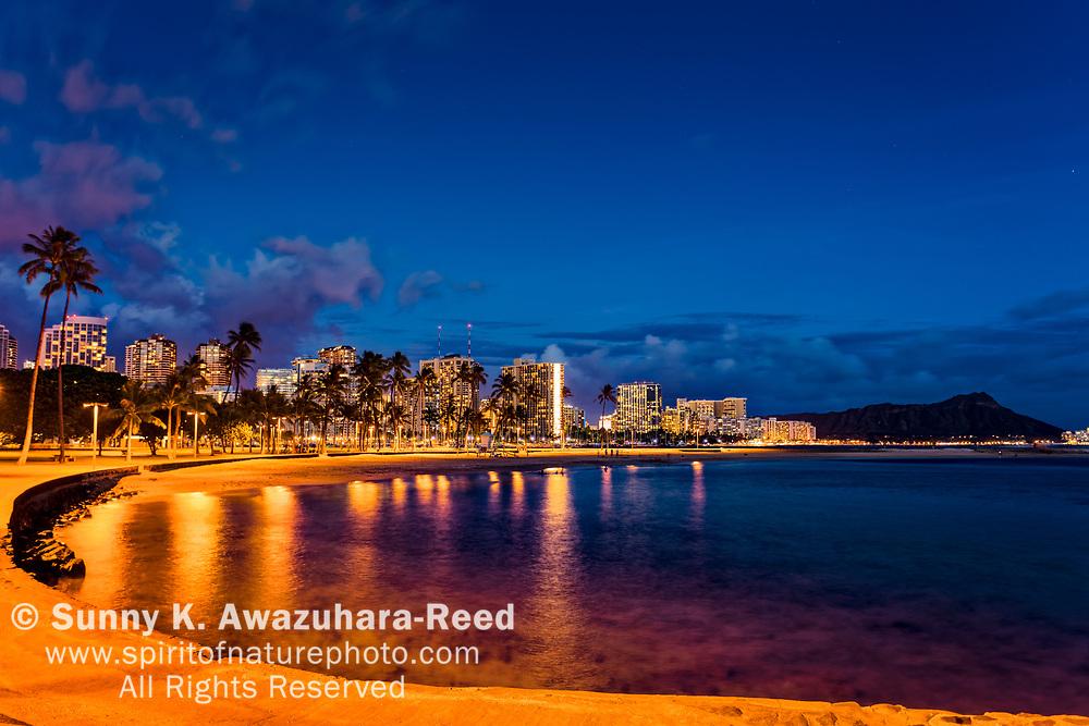 Magic Island Beach and Waikiki Skyline at night. Diamond Head is in the background. Honolulu, Oahu, Hawaii.