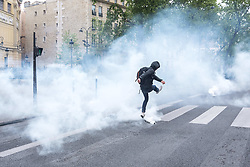 April 27, 2017 - Paris, France - A man kicks back a tear gas canister at police in Paris on April 27, 2017 during a demonstration against the results of the first round of the presidential election. (Credit Image: © Julien Mattia/NurPhoto via ZUMA Press)