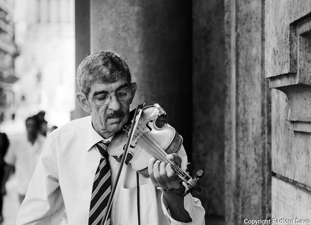A well dressed and well practiced musician on the streets of Rome plays for the passersby.