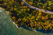A car drives though Cave Point County Park in Door County, Wisconsin during early fall.