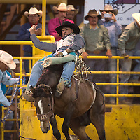 Kyle Charley of Lukachuchia holds on to Twin Peaks out of the bucking chute for a score of 77 in the bareback riding event Thursday at the Navajo Nation Indian Rodeo in Window Rock.