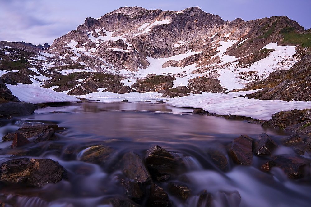 Water cascades over rocks at the outlet of a lake in an alpine basin used as a base camp for climbs of Glacier Peak in Glacier Peak Wilderness, Washington.