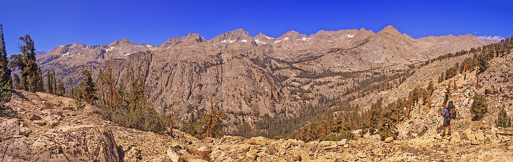 A backpacker, at lower right, disappears into the sheer scale of the mountain wilderness. The ridgeline is the eastern face of the Great Western Divide. <br /> <br /> Panoramic available up to  10419 x 3287 pixels.