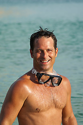 Shirtless wet man with goggles around his neck, laughing at the beach