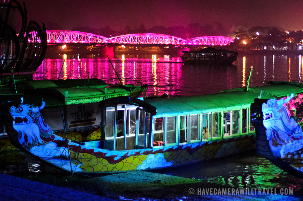A brightly painted tourist boat is docked against the shore in the foreground with the brightly illuminated Trang Tien bridge across the Perfume River in the background, while another boat passes down the river in between.