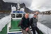 British tourists ride the local ferry up Reinefjorden from Reine, Moskenesoya, Lofoten Islands, Norway.