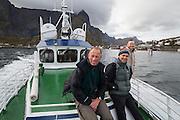 British tourists ride the local ferry up Reinefjorden from Reine, Moskenesoya, Lofoten Islands, Norway.