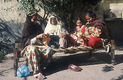 Three generations of women sitting on bed outside in the sunshine; knitting; talking and preparing vegetables,