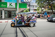 """15 JULY 2014 - BANGKOK, THAILAND: A """"tuk-tuk"""" or three wheeled taxi in Siam Square, a shopping and entertainment area in Bangkok. There is a range of shops and services, including tutor schools, restaurants, cafe, designer clothing boutiques, record stores, bookshops, Hard Rock Cafe and banks in the area. Siam Square is owned by Chulalongkorn University and is managed by its Property Management Office, known as the Chula Property.    PHOTO BY JACK KURTZ"""